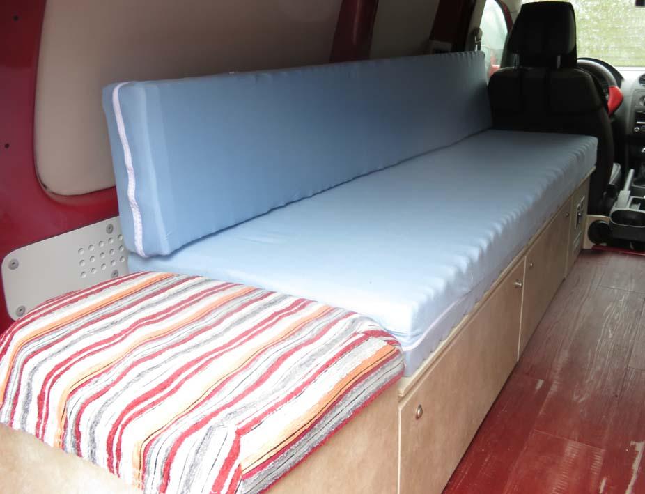 Matratzenteile im zusammengefahrenen Bett, Rückwand wird hochgestellt als Rückenlehne